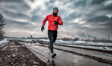Athlete running in dirty puddle at winter, outdoor exercise