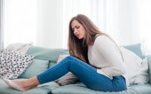 Mladá žena trpí bolesti břicha, zatímco sedí na gauči doma