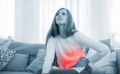Žena trpí bolesti břicha, zatímco sedí na pohovce v hom