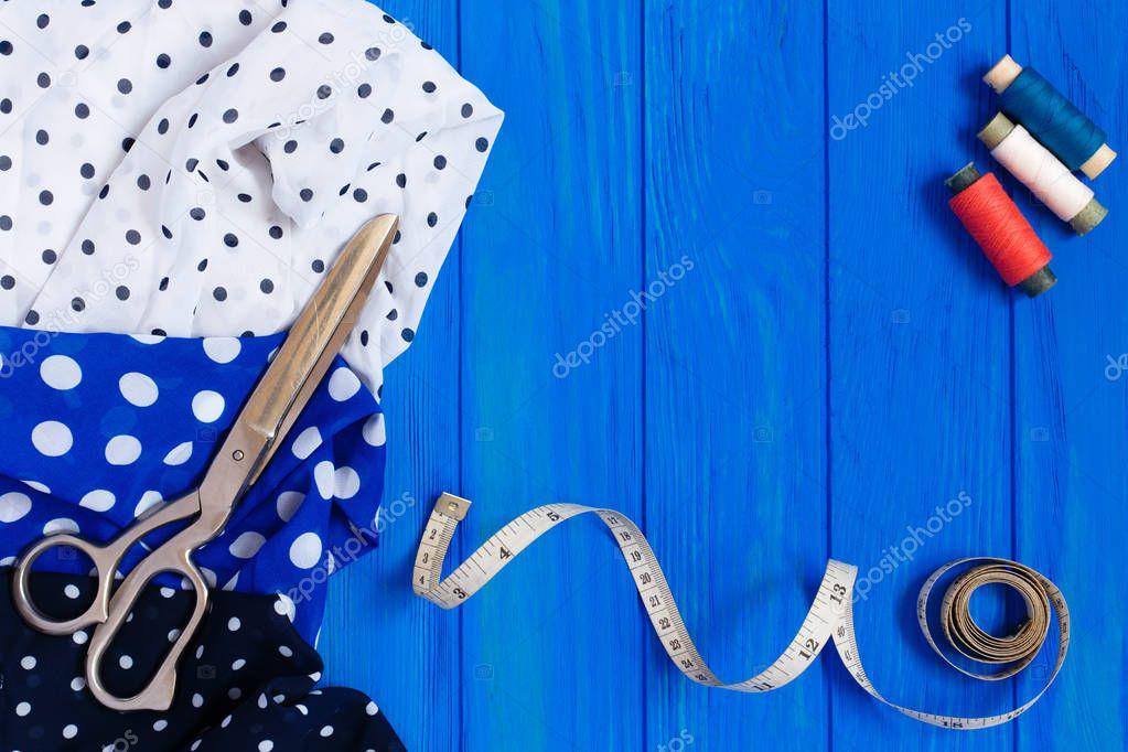 dotted fabrics, scissors, bobbins of threads, measuring tape, on