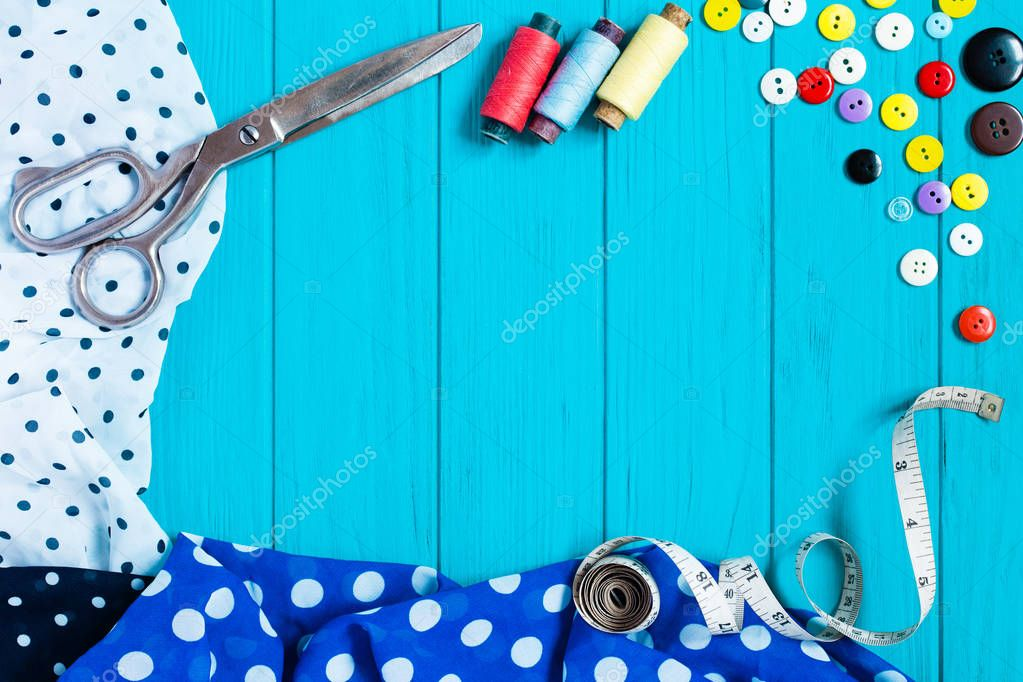 Dotted fabrics, scissors, buttons, measuring tape, on turquoise