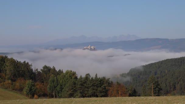 Spis hrad, kolem kterého protéká mlha, v pozadí jsou Vysoké Tatry. Časová prodleva 4K videa. Záběry jsou z podzimu.