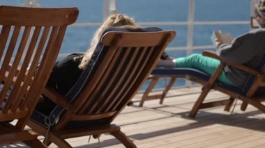 Sea Travel and Cruise Ship Relax. People Relaxing on Deckchairs During Transatlantic Cruise. Slow Motion Footage