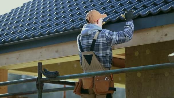 Střešní průmysl. Keramické dlaždice Dům střešní konstrukce. Stavební dělník na lešení.