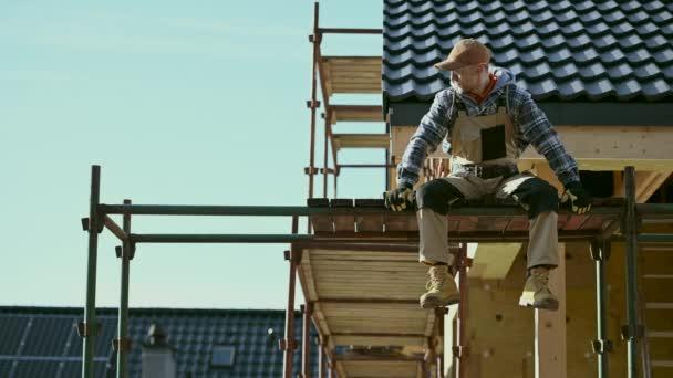 Bauarbeiter entspannt auf einem Baugerüst. Industrielles Thema.