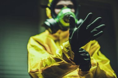 Hospital Worker Wearing Hazmat Suit and Hand Protection Gloves Preparing For Work During Global Pandemic.