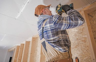 Caucasian Construction Contractor with Electric Drill Driver Attaching Drywall Elements to the House Ceiling. Finishing Home Interior.