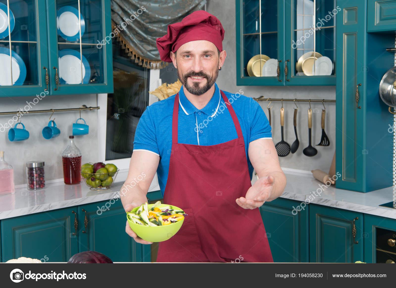 Lo Chef barbuto in grembiule e cappello fatto insalata. Uomo in cappello  tiene zolla gialla con insalata in mani sulla cucina. Insalata di verdure  cotto ... fd9fd31f7ba6