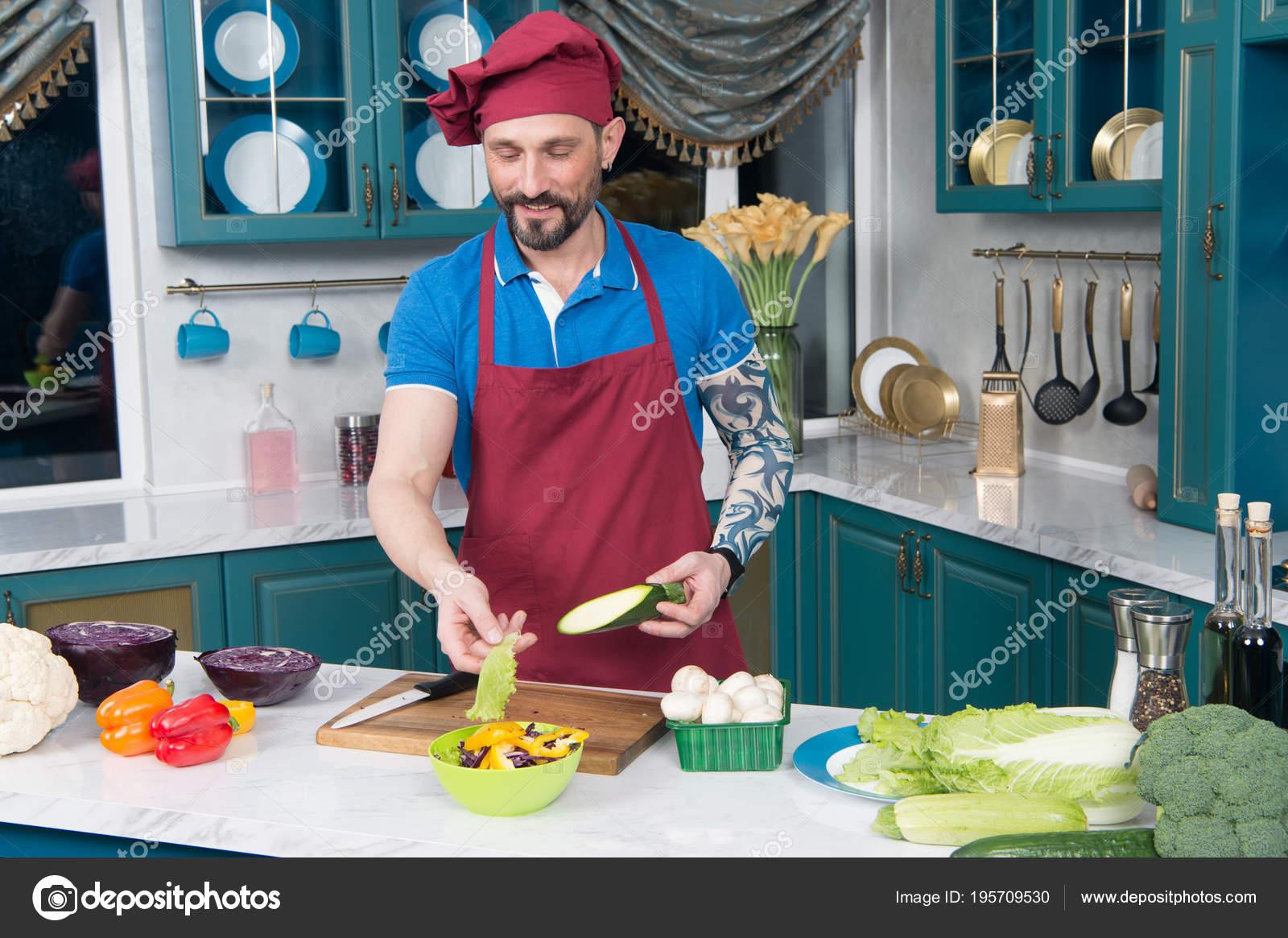Chef tatuato in grembiule e cappello cucina insalata. Ragazzo cucinare  Insalata di verdure con cavolo rosso e zucchine in zolla gialla. 2ecedf07233c