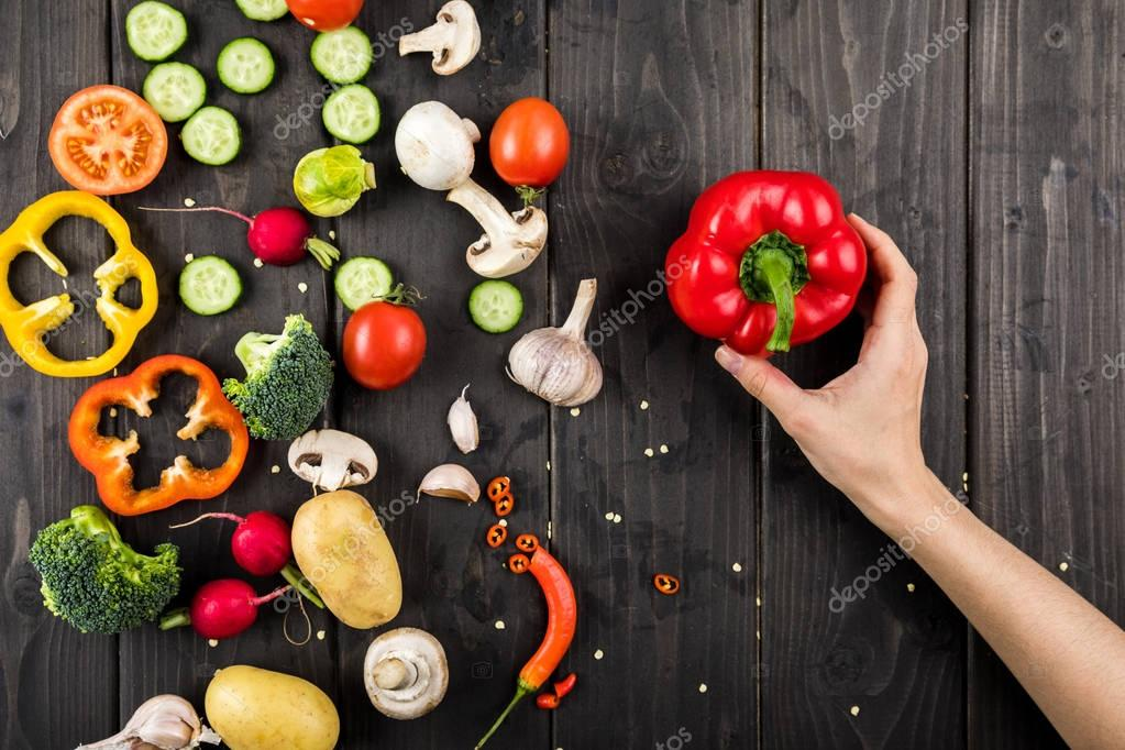 Fresh vegetables and hand with pepper