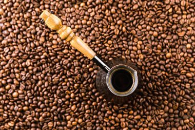 Top view of aromatic coffee beans and turk with beverage stock vector