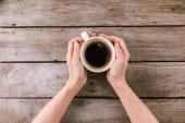 parní hrnek kávy v rukou