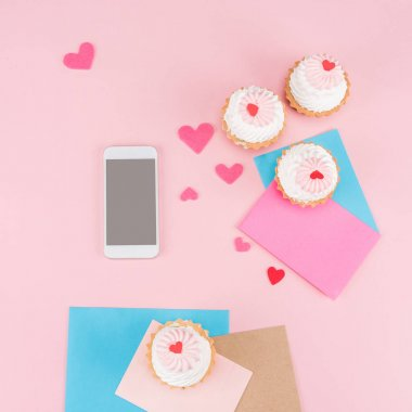 Delicious cupcakes and smartphone