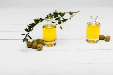 Close-up view of pure olive oil and green olives on wooden surface stock vector