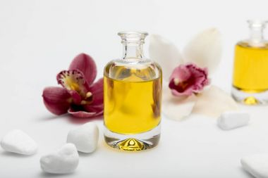 Close-up view of essential oil, white stones and orchids isolated on white stock vector
