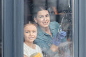 Photo Mother and daughter cleaning window