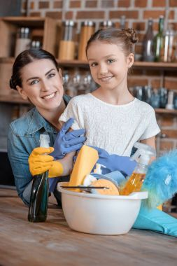 Portrait of happy mother and daughter in rubber gloves with cleaning supplies stock vector