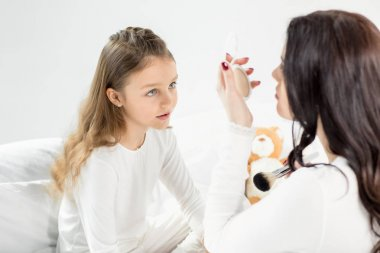 Mother and daughter with cosmetic mirror