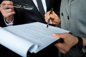 Businesspeople signing papers