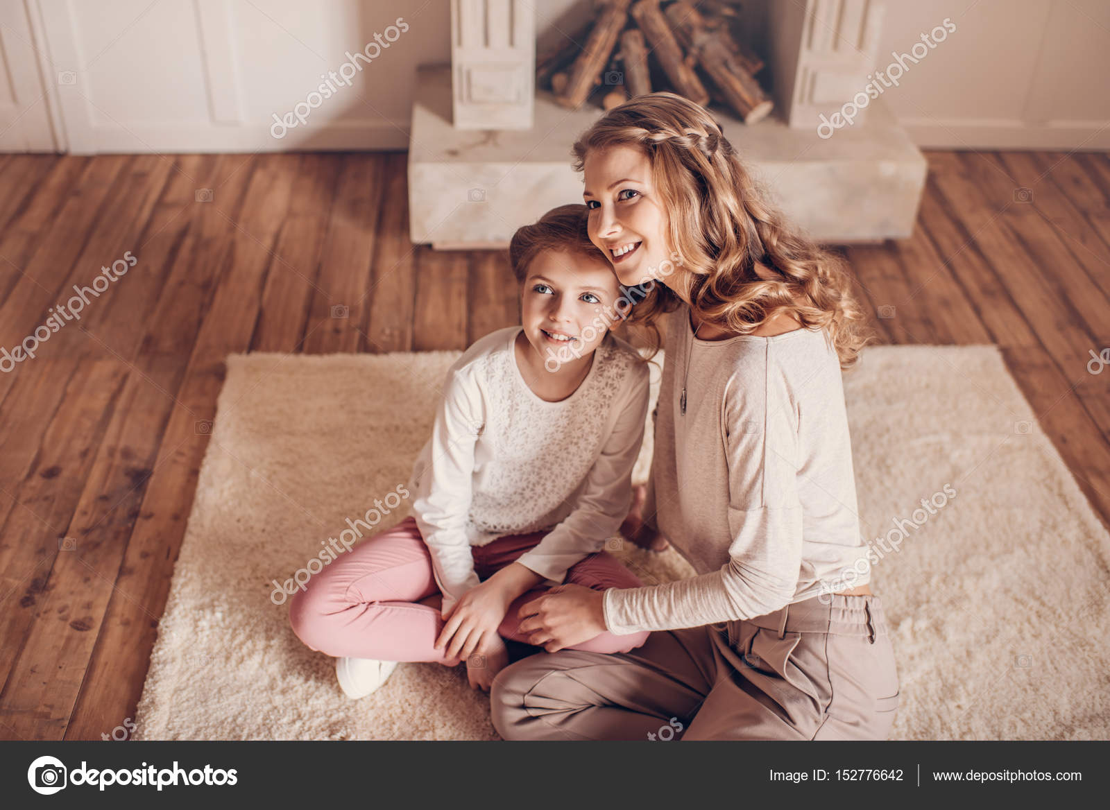 vue grand angle heureuse m re et fille assis ensemble sur le tapis et la recherche. Black Bedroom Furniture Sets. Home Design Ideas