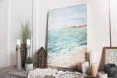 Obrázek moře, svíčky a ozdoby na poličce doma