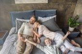 glücklich entzückende Tochter mit Mutter und Vater entspannt auf dem Bett zu Hause