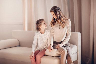 Beautiful mother and daughter sitting together on sofa and smiling each other