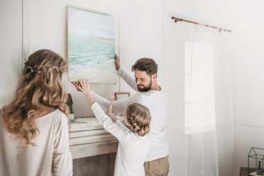 Happy family hanging picture of sea over the fireplace at home
