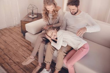 High angle view of happy family with one child spending time together on sofa at home
