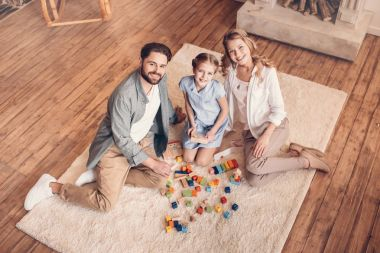 happy family playing with constructor and sitting on floor at home