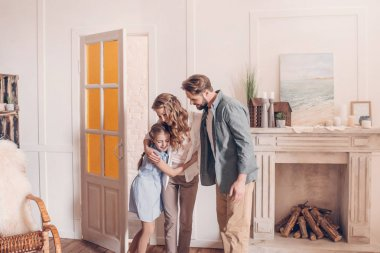 Happy family embracing and standing at home with fireplace behind