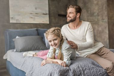 Happy adorable daughter and father sitting on bed at home