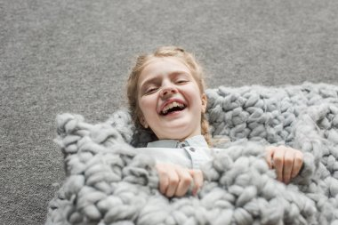 adorable girl laughing and lying on floor with grey knitted blanket