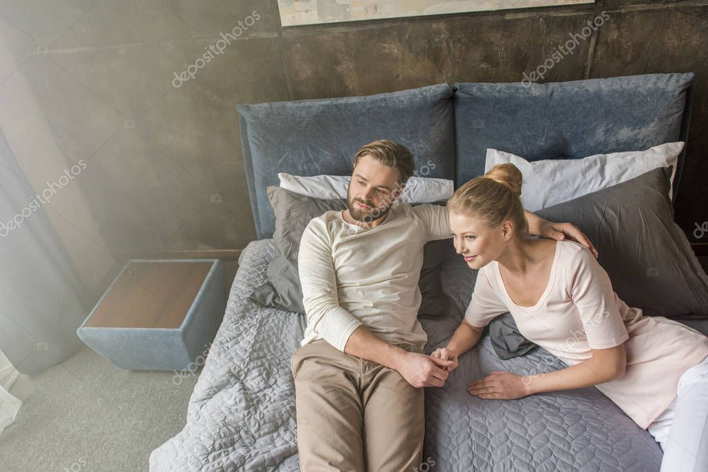 happy caucasian couple holding hands and relaxing on bed at home