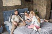 Fotografie šťastný roztomilý dcera s matkou a otcem relaxační na posteli doma
