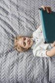 Fényképek imádnivaló lány segítségével digitális tábla és fekvő ágyban otthon