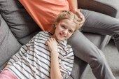 Šťastná holčička leží na otce nohy a usmívá se na kameru