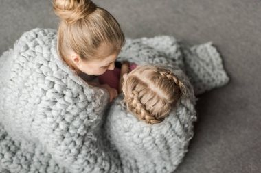 overhead view of mother and daughter hugging and sitting on floor with wool knitted blanket