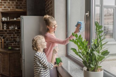 Happy mother and daughter cleaning window with rag and spray bottle together