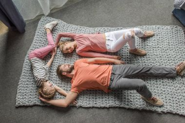 High angle view of happy family lying together on grey knitted carpet