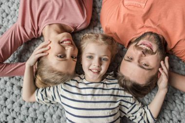 Top view of happy family with one child lying together on grey knitted carpet
