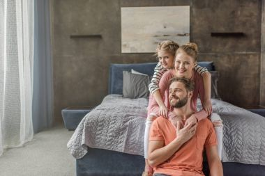 Happy young family with one child sitting together and hugging in bedroom