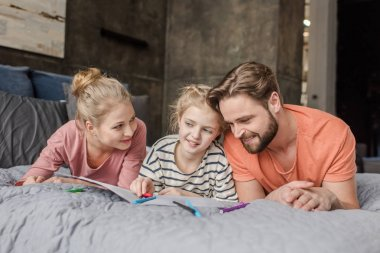 Happy parents lying on bed and looking at smiling daughter drawing