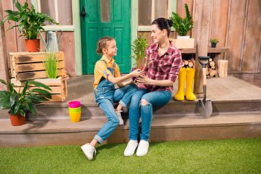 Happy mother and daughter with potted plant sitting together on porch and smiling each other