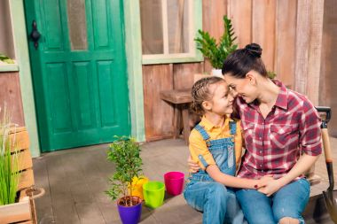 Happy mother and daughter sitting and holding hands on porch with potted plants
