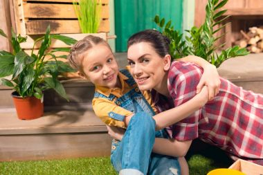 Happy mother and daughter hugging on green lawn and smiling at camera
