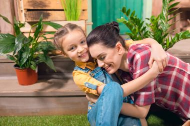 Happy mother and daughter hugging on porch with potted plants