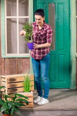 Young smiling brunette woman standing on porch with green plant in pot