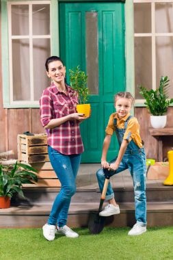 Smiling mother with potted plant and daughter with garden shovel standing on porch