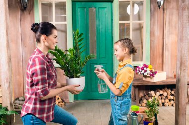 mother and daughter watering plant with spray bottle, standing on porch